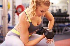 Молодая женщина работая с гантелями на спортзале, горизонтальном Стоковая Фотография RF