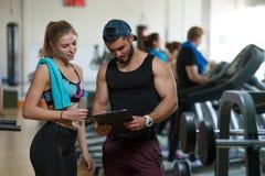Молодая женщина работая с личным тренером в спортзале Стоковое Изображение RF