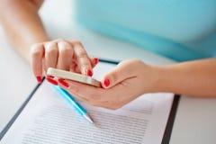Молодая женщина работая с мобильным телефоном над контрактом Стоковое Изображение