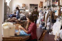 Молодая женщина работая с тканью в студии дизайна одежды Стоковые Фотографии RF