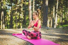 Молодая женщина размышляя в йоге положения лотоса практикуя в концепции свободы леса Стоковое фото RF