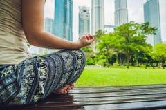 Молодая женщина размышляя в парке на предпосылке небоскребов Стоковые Фото