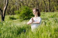 Молодая женщина размышляя в парке стоковое фото