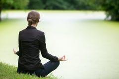 Молодая женщина размышляя на озере Стоковые Изображения