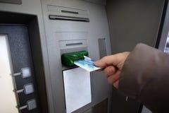 Молодая женщина разделяя деньги от кредитной карточки на ATM Стоковая Фотография RF