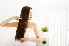 Молодая женщина расчесывая ее волосы в живущей комнате Стоковые Фото