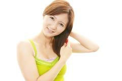 Молодая женщина расчесывая ее волосы стоковое изображение rf