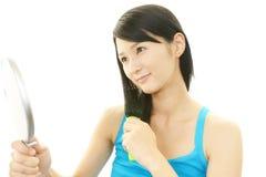 Молодая женщина расчесывая с щеткой для волос стоковое фото rf