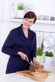 Молодая женщина режа ломтик хлеба в ее кухне Стоковое фото RF