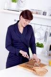 Молодая женщина режа ломтик хлеба в ее кухне Стоковые Изображения RF