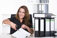 Молодая женщина режет лист бумаги с парой ножниц Стоковое фото RF