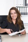 Молодая женщина режет лист бумаги с парой ножниц Стоковые Изображения RF