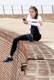 Молодая женщина резвится снаружи женщины сидя слушая к музыке Стоковое Изображение