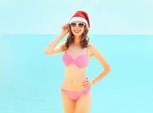 Молодая женщина рождества усмехаясь в красной шляпе santa на пляже над морем Стоковые Изображения