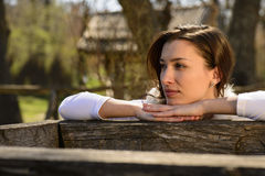 Молодая женщина рядом с деревянным колодцем Стоковая Фотография RF