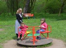 Молодая женщина свертывает 2 детей на карусели в парке Стоковые Фото