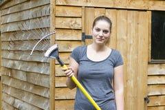 Молодая женщина сгребая траву в саде Стоковое Изображение