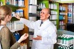 Молодая женщина сервировки аптекаря в фармации Стоковое Изображение