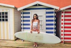 Молодая женщина серфера с верхней частью и бикини держа surfboard Стоковые Изображения RF