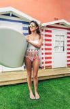 Молодая женщина серфера с верхней частью и бикини держа surfboard Стоковая Фотография