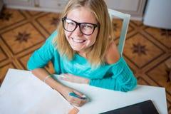 Молодая женщина сидит на таблице с компьтер-книжкой и обработкой документов Стоковая Фотография