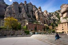 Молодая женщина сидит на шагах среди зданий монастыря Монтсеррата расположенных между огромными утесами в Каталонии, Испании Стоковые Фото