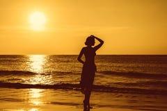 Молодая женщина силуэта на пляже на заходе солнца Стоковое Изображение RF