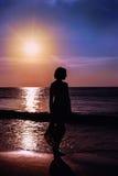 Молодая женщина силуэта на пляже на заходе солнца Стоковые Изображения RF