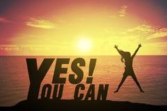 Молодая женщина силуэта скача и поднимая вверх ее рука о счастливой концепции на УТВЕРДИТЕЛЬНОМ ОТВЕТЕ ВЫ МОЖЕТЕ отправить СМС стоковая фотография rf