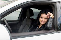 Молодая женщина сидя внутри автомобиля усмехаясь на камере Стоковое Изображение