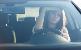 Молодая женщина сидя в автомобиле Стоковые Изображения