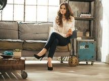 Молодая женщина сидя в квартире просторной квартиры Стоковые Изображения RF