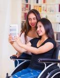 Молодая женщина сидя в кресло-коляске используя чернь при ассистент стоя рядом с ей, обоими усмехаясь счастливо показывающ Стоковые Фотографии RF