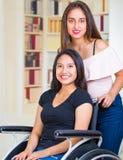 Молодая женщина сидя в кресло-коляске при ассистент стоя рядом с ей, обоими усмехаясь счастливо показывающ положительную ориентац Стоковая Фотография RF
