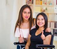 Молодая женщина сидя в кресло-коляске при ассистент стоя рядом с ей, обоими усмехаясь счастливо показывающ положительную ориентац Стоковые Изображения