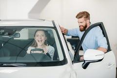 Молодая женщина сидя в новом автомобиле и человеке стоя близко Стоковое фото RF