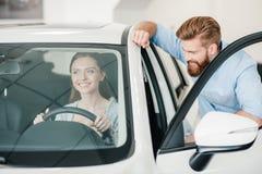 Молодая женщина сидя в новом автомобиле и человеке стоя близко Стоковое Изображение