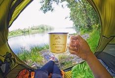 Молодая женщина сидя в шатре и выпивая чае пока смотрящ на реке Desna Стоковое Изображение