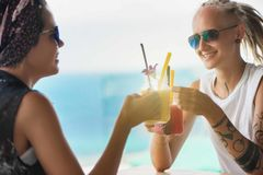 Молодая женщина 2 сидя в smoothie кафа выпивая стоковые изображения