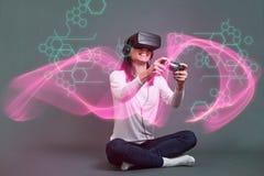 Молодая женщина сидя и имея потеха играя vid виртуальной реальности стоковые фото