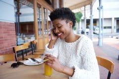 Молодая женщина сидя на внешнем кафе говоря на сотовом телефоне Стоковые Изображения