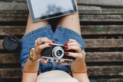 Молодая женщина сидя на деревянной скамье Стоковые Изображения