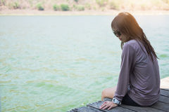 Молодая женщина сидя на деревянном фронте сплотка себя голубое wat Стоковая Фотография RF