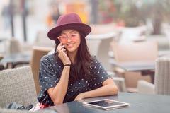 Молодая женщина сидя на кафе и беседе к телефону Стоковая Фотография RF