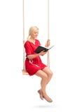 Молодая женщина сидя на качании и читая книгу Стоковые Фотографии RF