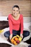 Молодая женщина сидя на ковре и наслаждаясь плодоовощами стоковое фото