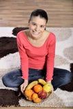 Молодая женщина сидя на ковре и наслаждаясь плодоовощами стоковое изображение rf