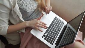 Молодая женщина сидя на кресле используя компьтер-книжку и усмехаясь, конец-вверх рук Перста на клавиатуре видеоматериал