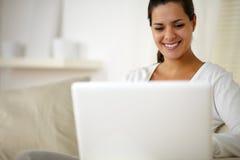Молодая женщина сидя на кресле и работая на компьтер-книжке Стоковое Изображение
