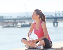 Молодая женщина сидя на речном береге Стоковое Фото